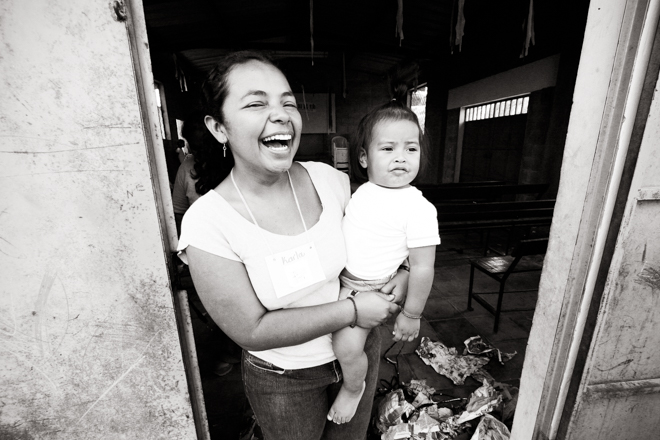 Salvadorean woman, laughing, holding toddler in the doorway