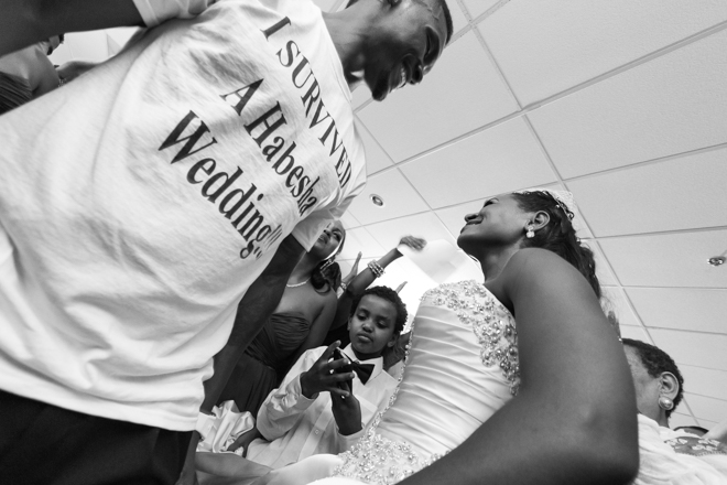 "Groom with ""I survived a Habesha Wedding"" t-shirt on, dancing with his bride."