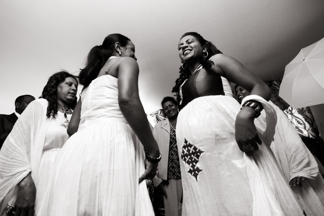 Two women dancing, one of them pregnant, dressed in traditional Ethiopian wedding attire.