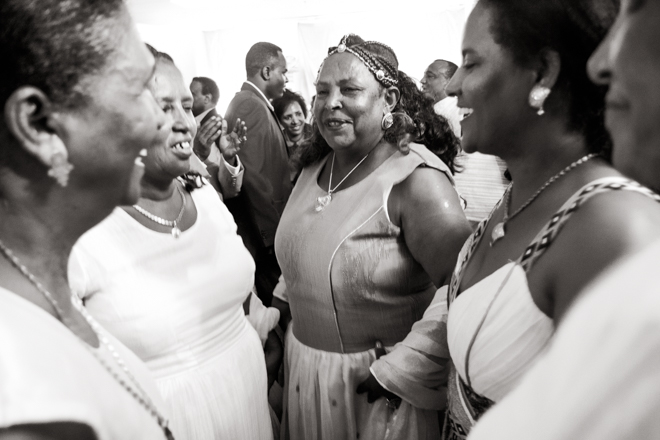 Five older, Ethiopian women dancing at the reception, mother of the bride in the middle.