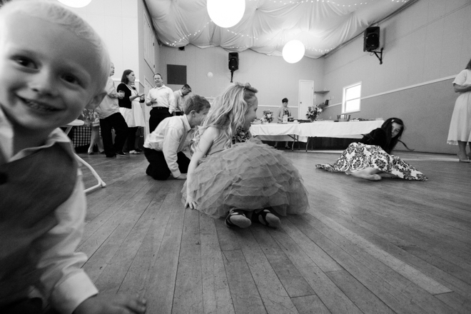 Kids sliding towards the camera on the hardwood floor at a wedding reception.