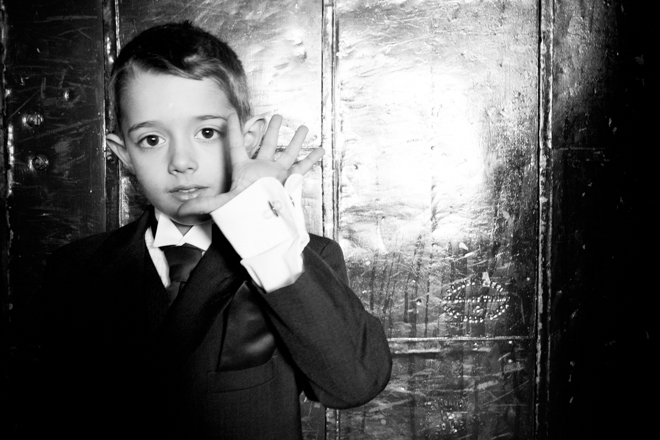 Little boy standing against a metal door holding up five fingers.