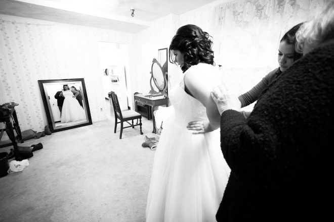 Two women helping the bride button up her wedding dress while she looks in a mirror across the room.
