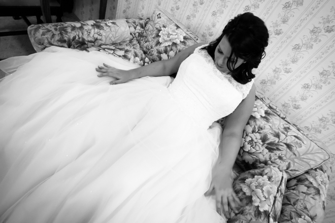 Bride looking down at her wedding dress, sitting on vintage couch.