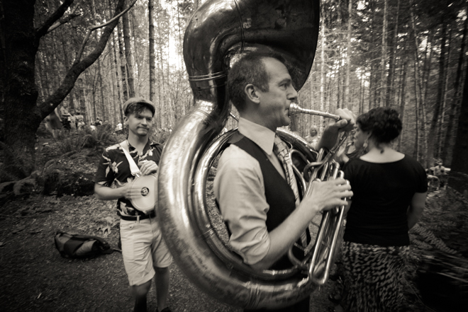 Many playing tuba walking through the woods.