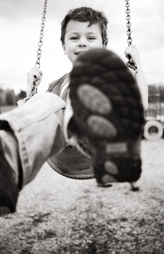 Little boy on a swing, swinging towards the camera.