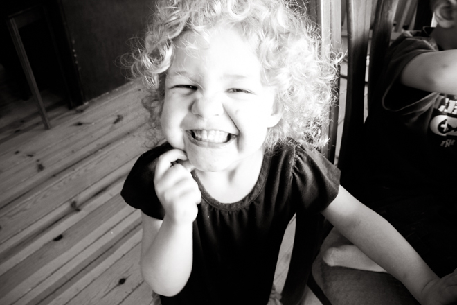 Little girl with blonde curly hair with a huge smile on her face.