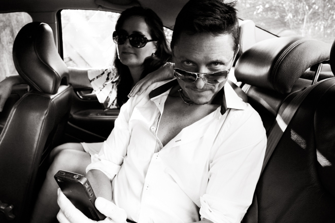 Man and woman in a car, both with sunglasses on being coy.