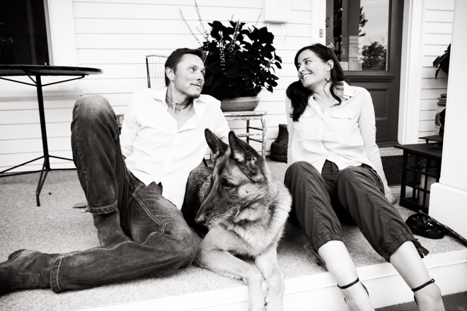 A man and a woman sitting on a porch with a German Shepherd sitting in between them.