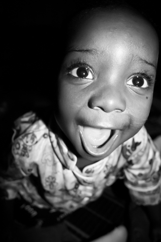 Little girl, up close, smiling with huge, beautiful eyes.