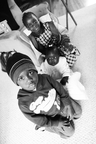 Three Sudanese kids sitting on the floor.