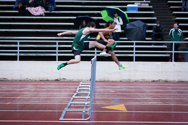 Male hurdlers coming over the high hurdles.