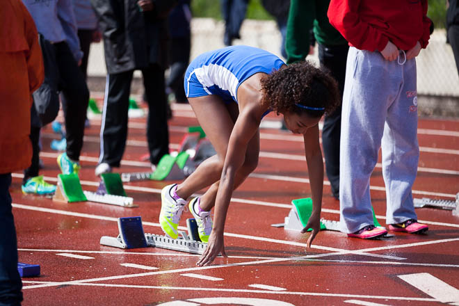 Female runner from Curtis High School in the blocks.