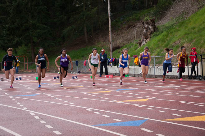 Male athletes from various Washington High Schools in the 100m race.