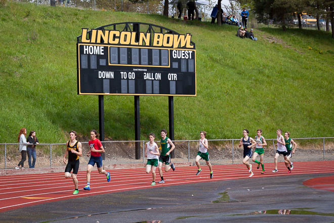 Male runners from various WA State High Schools running under the Lincoln Abes home sign.