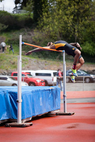 Male high jumper from Lincoln High School coming over the bar.