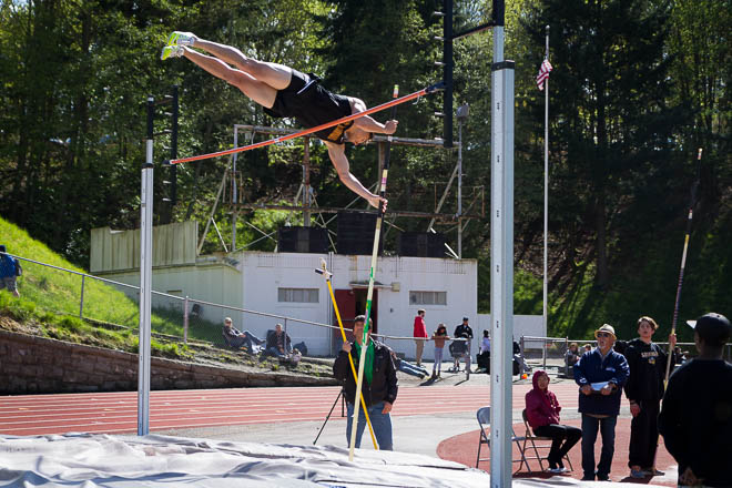 Male pole vaulter coming over the bar.