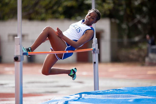 Female high jumper from Curtis HS at the top of her jump.