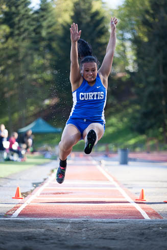 Female long jumper from Curtis HS flying through the air.