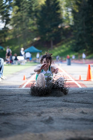 Female long jumper from Tumwater HS landing in the sand.